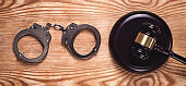 Metal handcuffs and judge gavel on wooden background. Crime and Law Concept