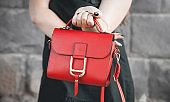 Woman holding red leather bag. Fashion