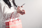 Girl using smartphone and holding shopping bag. Shopping