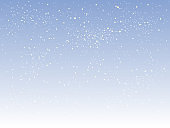 Falling white snow with blue winter sky.