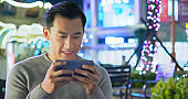 asian man play mobile game