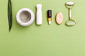 Face roller and skin care products on green background. Copy space. Flat  lay