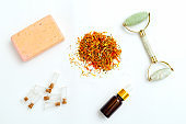 Dried marigold flowers and face roller on white background. Apothecary