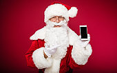 Your present. Happy Santa Claus is posing, showing a smartphone in his left hand, and pointing at it with his right index finger.