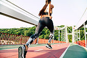 Running young woman in sport clothes outdoors