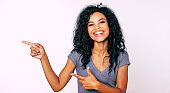 Just look! Extremely happy African ethnic girl with messy black hair in a gray t-shirt is looking at the camera and pointing with finger guns to the left.