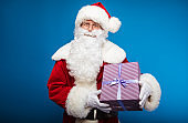 Christmas Eve. Carrying someone's dream. Real Santa Claus is posing with a striped purple gift box, which he is holding in his hands on the left side of him, looking at the camera and smiling kindly.