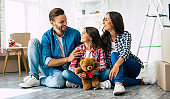 So happy together. Cheerful young family of father, mother and daughter sitting on the floor in the living room of their new house surrounded by boxes.