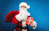 Christmas and New year concepts. Happy beautiful Santa Claus in red costume is posing over blue winter background.