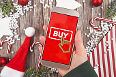Concept for Christmas seasonal online shopping and sales with hand holding cell phone with 'Buy' sign button in red background in front of wooden desk with seasonal decorations