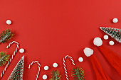 Traditional Christmas season flat lay with candy canes, snowballs, pine branches, santa hats and small Christmas trees on red background with copy space