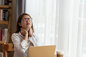Young businesswoman is having pain in neck at work