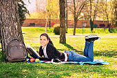 Girl in a park reading a book