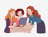 Three young women sitting at the table and looking for something on the Internet