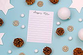 Concept for Christmas shopping with top view flat lay with empty shopping check list and seasonal decorations like tree baubles, snowflakes, stars and for cones on blue background