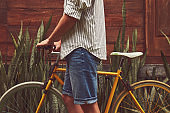 Attractive man standing with old bicycle.