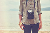 Fashionable woman holding camera on the beach.