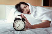 Turning off Sound or Snoozing The Alarm Clock Concept, Beautiful Woman Waking Up in The Morning at Bedroom While Her Hand is extending Alarm of Timer Clock.