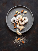 Christmas biscuits and almonds on a gray plate, rustic style