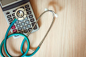 Stethoscope on calculator of health checkup insurance statement concept., Medical equipment for business healthcare and medicine on table., Occupation doctor.