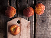 Peaches colorful arrangement on cutting board and wooden table