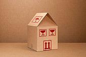 Moving home. Cardboard box shaped house.