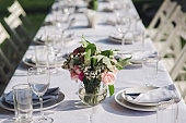 A large white long table with chairs, decorated with fresh flowers, with plates, glasses and forks, stands in a park with green grass. Wedding decorations and details. Preparing for a wedding party.