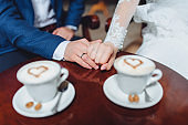 A newlywed couple is sitting in a beautiful cafe for a cup of coffee. White cups with cappuccino foam. Heart shape.