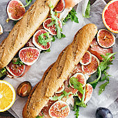 Sandwich prosciutto mascarpone cheese figs wooden table top view