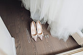 Beautiful pink shoes of the bride stand on the wooden floor near the white dress, golden rings and wedding jewelry.