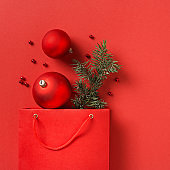 Christmas red shopping paper bag with decoration on red background copy space top view