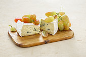 Bavaria blue cheese with grapes on a wooden board close up