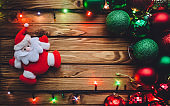 Christmas decorations. Christmas background with Santa Claus, Christmas balls, and garland with colored lights on a brown wooden board. Postcard concept.