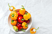 Yellow and red bell peppers in plate on white background top view