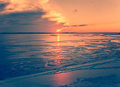Winter evening landscape at sunset. Orange sun over the river. Icy water.