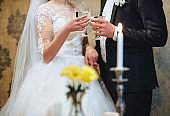 Newlyweds with glasses in hands celebrate their wedding close-up. Champagne for groom and bride. Clink glasses.