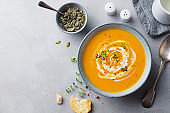 Pumpkin and carrot soup with cream on grey stone background. Copy space. Top view.
