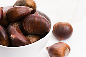 Bowl of chestnuts on a white background