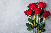 Red roses on grey stone background. Love concept valentines day. Copy space. Top view.