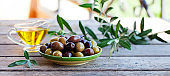 Assortment of fresh olives and olive oil in glass jug on wooden background. Copy space.