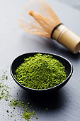 Matcha, green tea powder in black bowl with bamboo whisk on slate background.