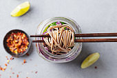 Noodles soba salad, soup with vegetables, tofu and chicken in jars. Grey background. Close up. Top view.