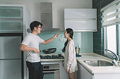 an asian chinese couple cooking in the kitchen and husband giving his wife a taste of his cooked food