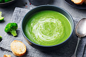 Broccoli cream soup in a bowl with toasted bread. Go green concept. Close up.