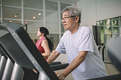 an asian chinese active senior man exercising with his granddaughter in gym with treadmill