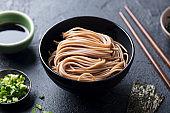 Soba noodles on a black bowl. Slate background. Close up.