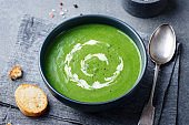 Broccoli cream soup in a bowl with toasted bread. Go green concept