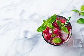 Raspberry cocktail, fizz, lemonade, ice tea with fresh mint. Marble background. Top view. Copy space