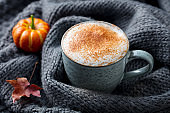 Pumpkin latte with spices. Grey knitted background. Close up.