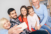 Group of people sitting at home, making selfie on smartphone